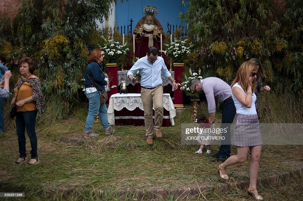 People stand past an altar with a Virgin in a street covered with grass during the Corpus Christi celebrations in El Gastor, southern Spain on May 29, 2016. The village of El Gastor celebrate the feast of Corpus Christi (or Body of Christ in Latin) covering the streets and facades of houses with branches of trees and grass. / AFP / JORGE