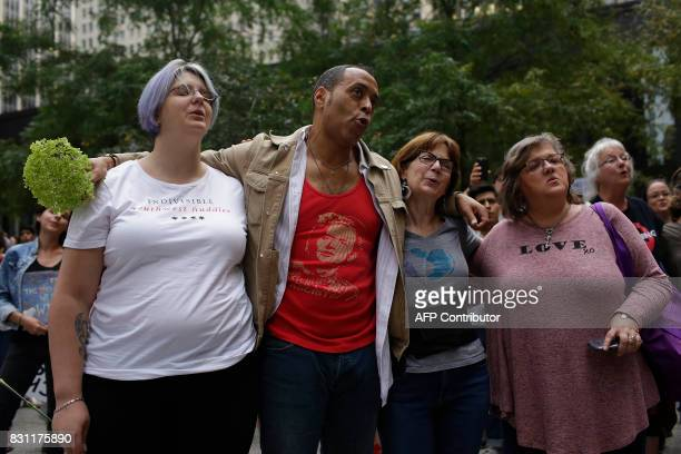 People stand shoulder to shoulder as they sing during a vigil August 13 2017 in Chicago Illinois for the victims in the previous day's violent...