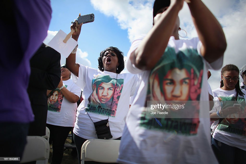 People stand together during the 'March for Peace' at Ives Estate Park in honor of the late Trayvon Martin on February 9, 2013 in Miami, Florida. Martin was killed by George Zimmerman on February 26, 2012 while Zimmerman was on neighborhood watch patrol in the gated community of The Retreat at Twin Lakes in Sanford, Florida.