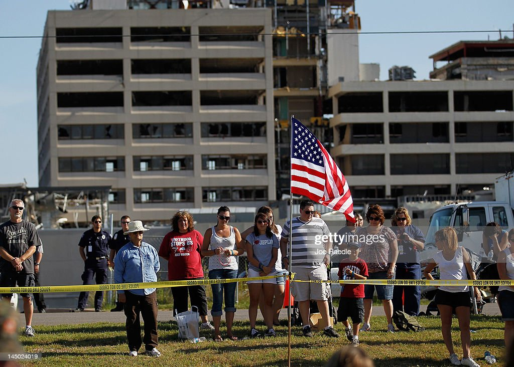 People stand together in front of the ruins of St. John's Medical Center during a moment of silence at 5:41 p.m. which was when the monstrous tornado first hit the city a year ago to the day on May 22, 2012 in Joplin, Missouri. The EF-5 tornado devastated the area leaving behind a path of destruction along with 161 deaths and hundreds of injuries, but one year later there are signs that the town is beginning to recover.