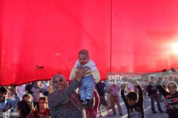 People stand under a giant Turkish flag at Istanbul's central Taksim Square on July 19 2016 in Istanbul Turkey Clean up operations are continuing in...