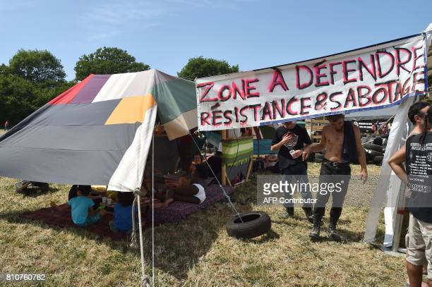 People stand under a sign reading 'Zone to defend Resistance and sabotage' during a twoday meeting organised by opponents to a controversial...