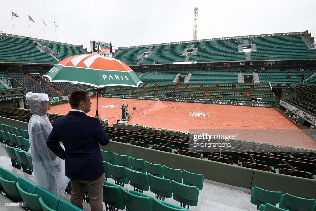 People stand under an umbrella as rains falls over the Roland Garros stadium during the Roland Garros 2016 French Tennis Open in Paris on May 31, 2016. / AFP / Eric FEFERBERG