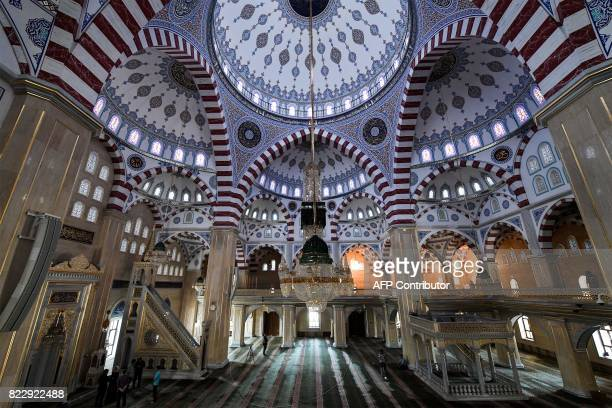 People stand under the dome of the Heart of Chechnya Akhmad Kadyrov Mosque one of the largest mosques in Russia in central Grozny on July 26 2017 /...