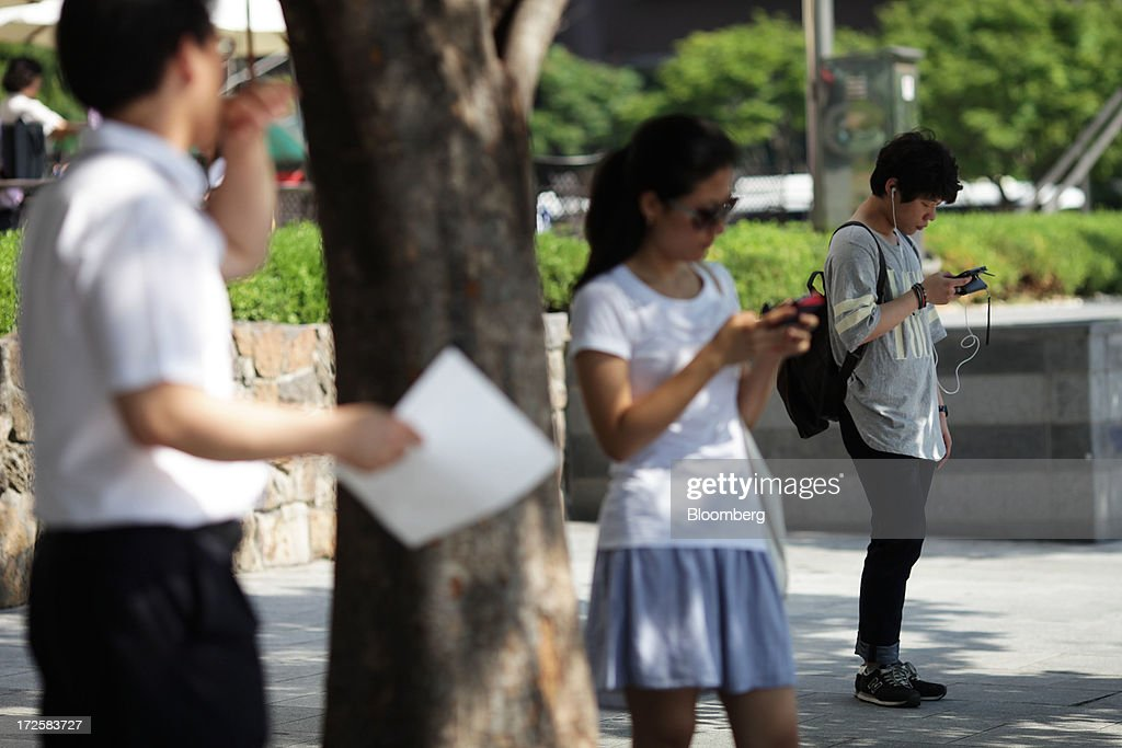 People stand using their smartphones near a bus stop at Gwanghwamun Square in Seoul, South Korea, on Wednesday, July 3, 2013. Samsung Electronics lost $25.3 billion in market capitalization last month, more than the value of competitor Sony Corp., as sales of its flagship Galaxy S4 smartphone fell short of investor expectations. Photographer: Woohae Cho/Bloomberg via Getty Images
