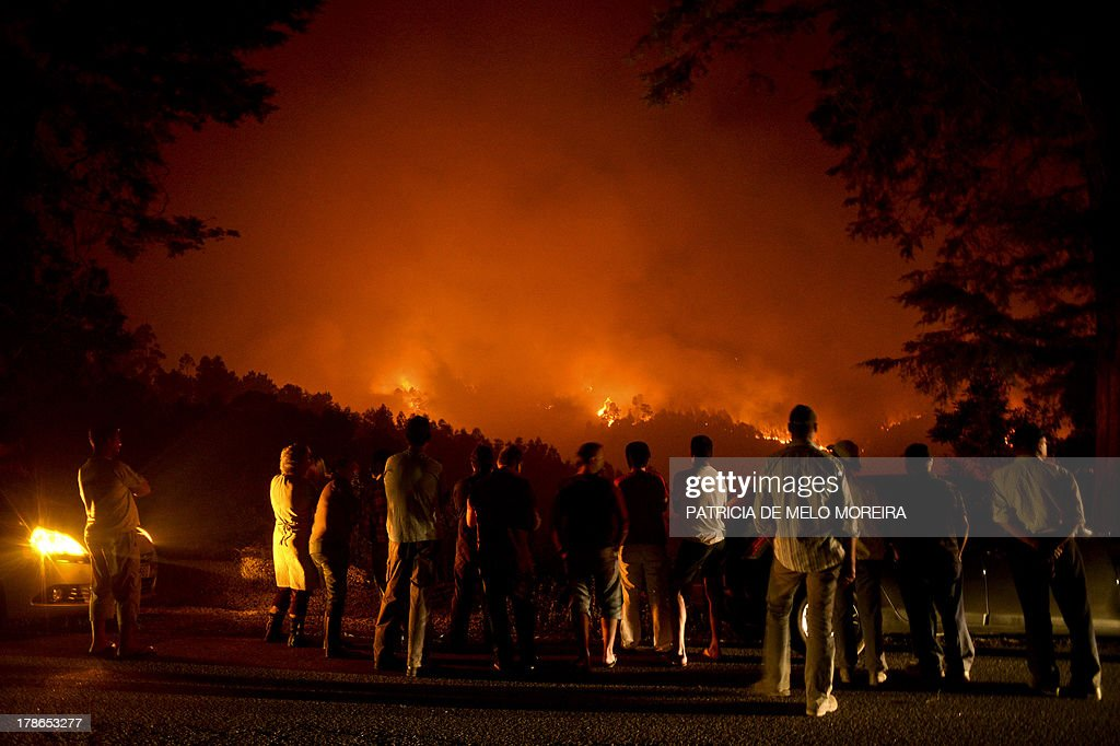 People stand watching a wildfire in Santiago de Besteiros, near Caramulo, central Portugal, on August 30, 2013. Five Portuguese mountain villages were evacuated overnight as forest fires intensified in the country's north and centre, officials said today. As many as 1,400 firefighters were dispatched Thursday to tackle the blaze in the mountains and another raging further north in the national park of Alvao, where 2,000 hectares (4,900 acres) of pine forest have already been destroyed, according to the local mayor. AFP PHOTO / PATRICIA DE MELO MOREIRA