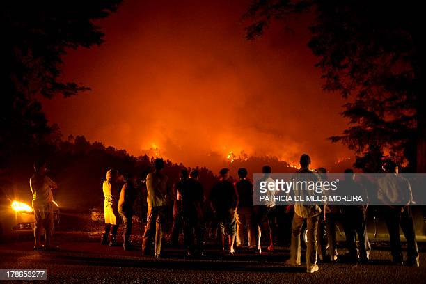 People stand watching a wildfire in Santiago de Besteiros near Caramulo central Portugal on August 30 2013 Five Portuguese mountain villages were...
