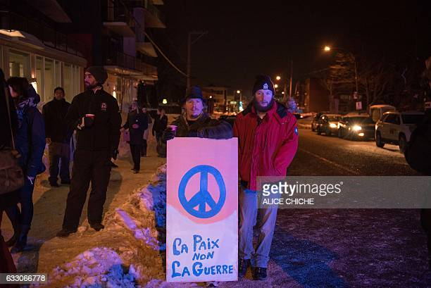 People stand with a peaceful sign near the Québec City Islamic cultural center after a shooting occurred in the mosque on SainteFoy Street in Quebec...