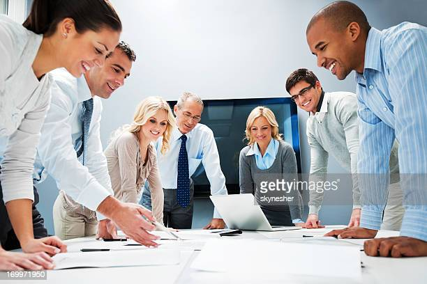 People standing around a table with a laptop