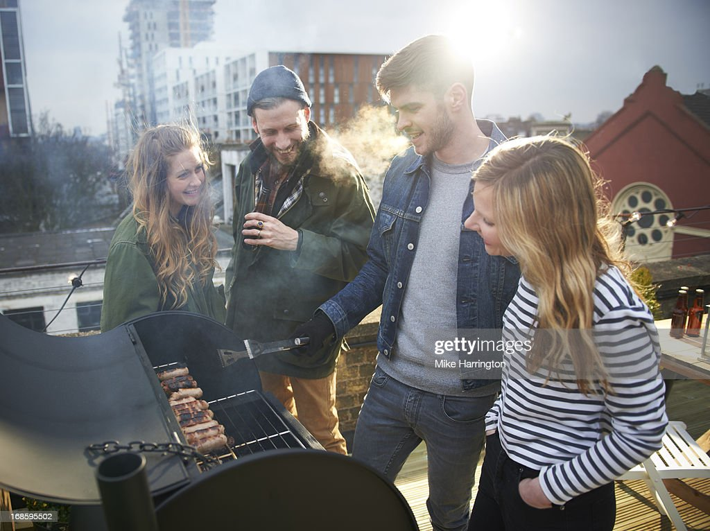 People standing around barbecue in roof garden.