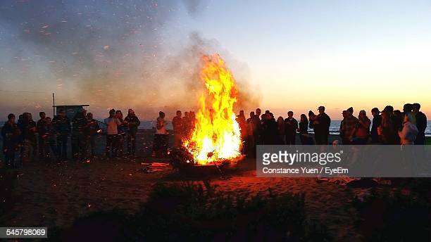 People Standing By Bonfire At Dusk