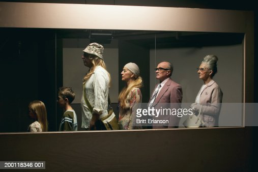 People standing in line behind glass partition : Stock Photo