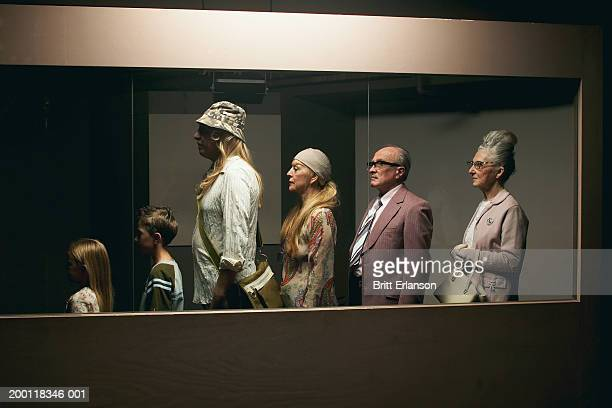 People standing in line behind glass partition