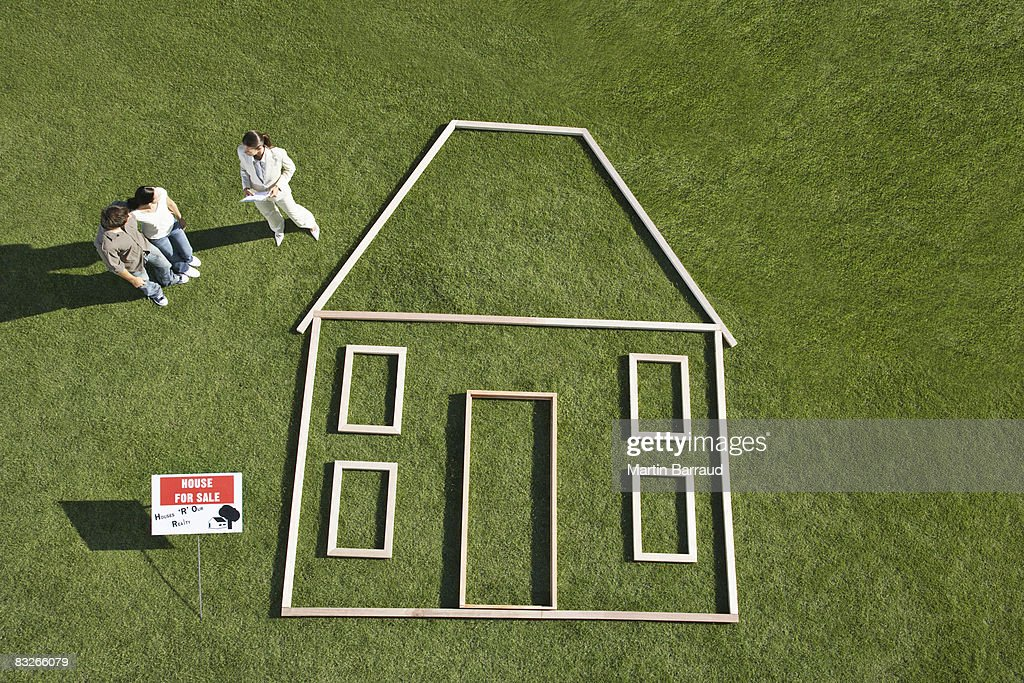 People standing near 'for sale' sign and house outline : Stock Photo