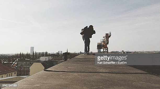 People Standing On Ledge Taking Picture With Camera