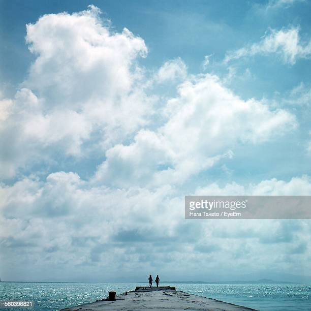 People Standing On Pier At Sea Against Cloudy Sky