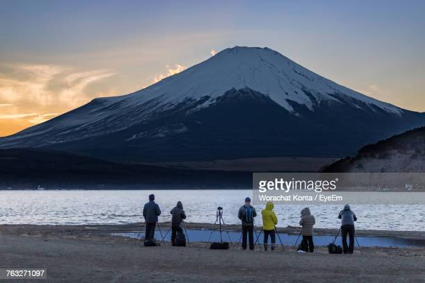 People Standing On Riverbank Against Snowcapped Mountains During Sunset