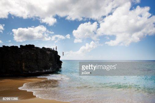 People standing on rock, woman jump into ocean