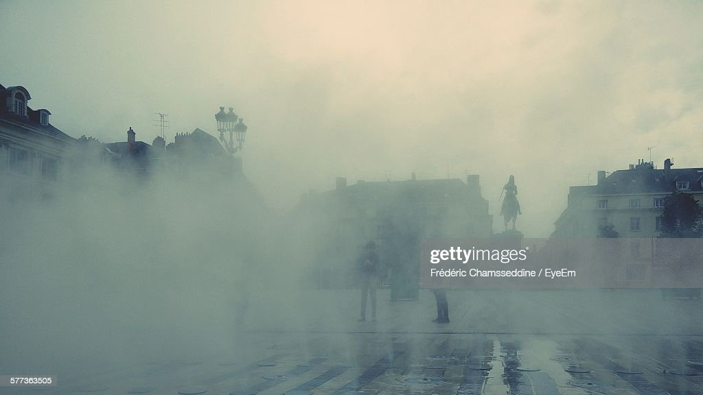 People Standing On Street Covered With Smoke