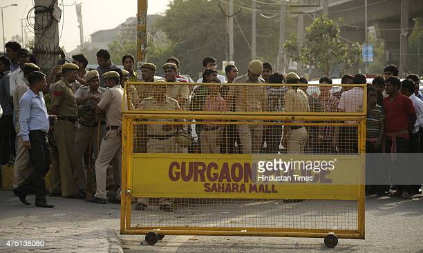 People standing outside the Sahara mall after a bomb scare call on May 29 2015 in Gurgaon India Some miscreant called the police control room and...