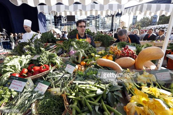 People stands at an ephemeral market during the festivities marking the 25th anniversary of French chef Alain Ducasse's restaurant 'Le Louis XV' on...