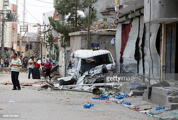 People stands next to a van damaged during the clashes between Turkish forces and militants of the Kurdistan Workers' Party in the Kurdishmajority...