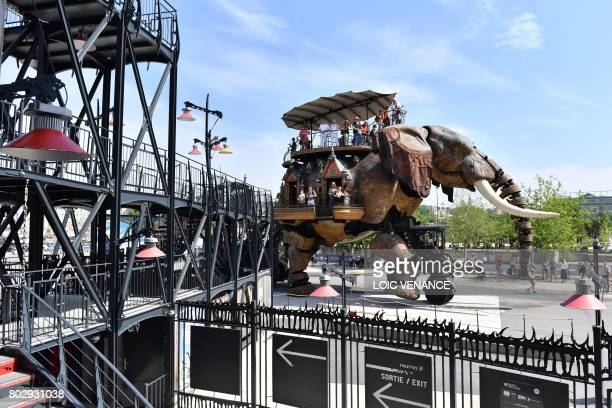 People stands on a mechanical elephant made of wood and steel at 'Les Machines de L'Ile' in Nantes western France on June 20 2017 It walks its 48ton...