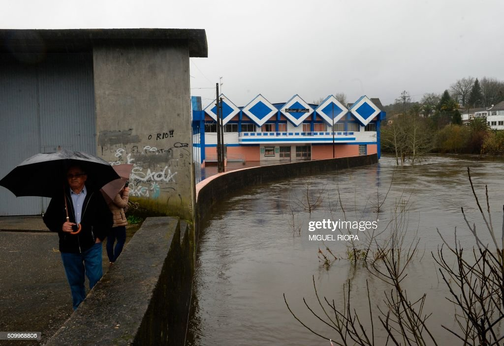 People stands with umbrellas past a flooded area next to the river Tea in Ponteareas, northwestern Spain, on February 13, 2016. / AFP / AFP or licensors / MIGUEL RIOPA
