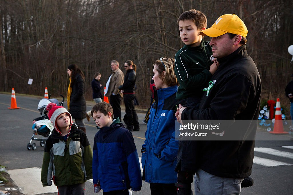 People stare in silence at a memorial for those killed in the school shooting at Sandy Hook Elementary School on December 24, 2012 in Newtown, Connecticut. Donations and letters are pouring in from across the country as the town tries to recover from the massacre.