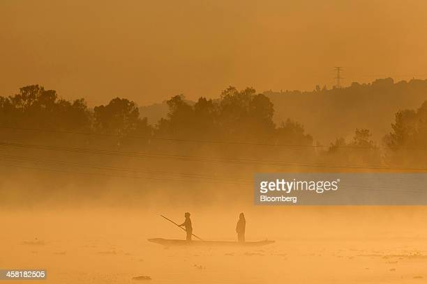 People steer a 'trajinera' or gondola at dawn past one of the the artificial islands known as 'chinampas' on a canal at Lake Xochimilco in Mexico...