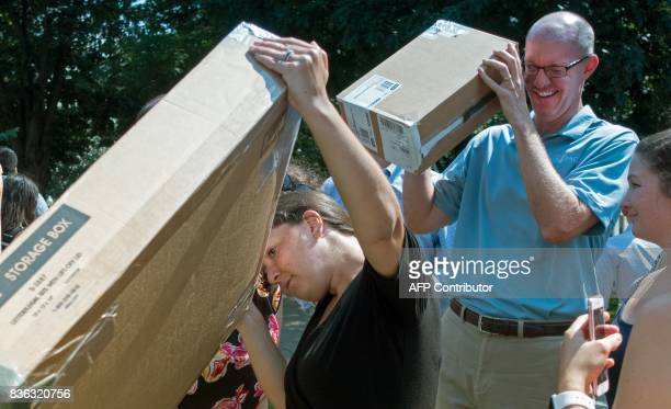 People step outside their workplace for a few minutes to look up at the partial solar eclipse with viewing boxes in McPherson Square in Washington DC...