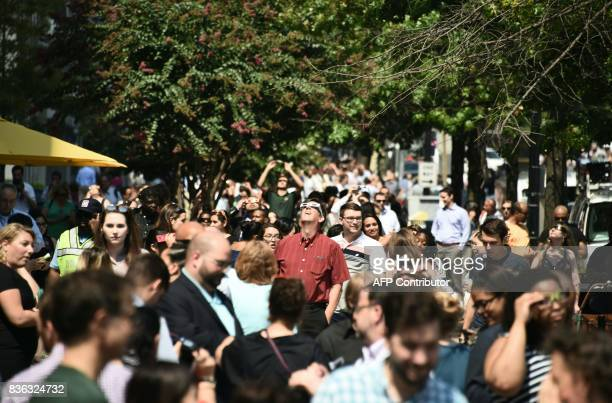 People step outside their workplace for a few minutes to look up at the partial solar eclipse in downtown Washington DC August 21 2017 The Great...