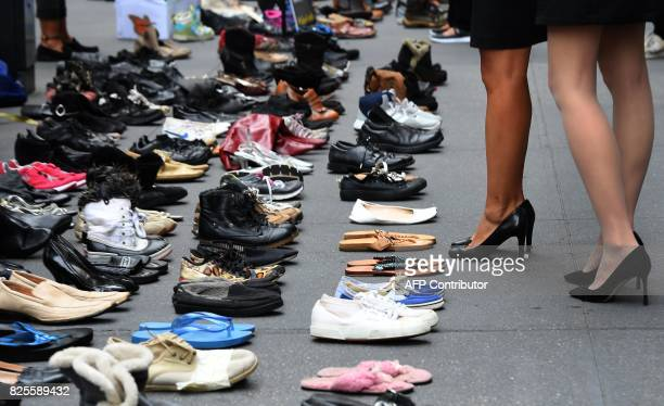 People stop and look as rows of shoes are placed in front of JPMorgan Chase on park Avenue in New York on August 2 2017 during a protest by...