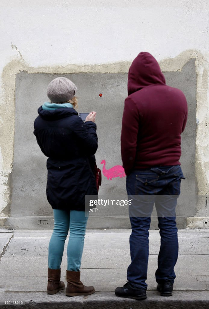 People stop and look at a section of a wall where celebrated street artist Banksy's 'Slave Labour' graffiti artwork was removed in north London on February 23, 2013. The work that showed a young boy using a sewing machine to make the British flag has been carefully removed and will be auctioned in Miami where it's expected to fetch around 328,000 GBP (500,000 USD). Residents of the North London area have reacted angrily to the removal of the work, but the auction house says the piece was acquired legally.