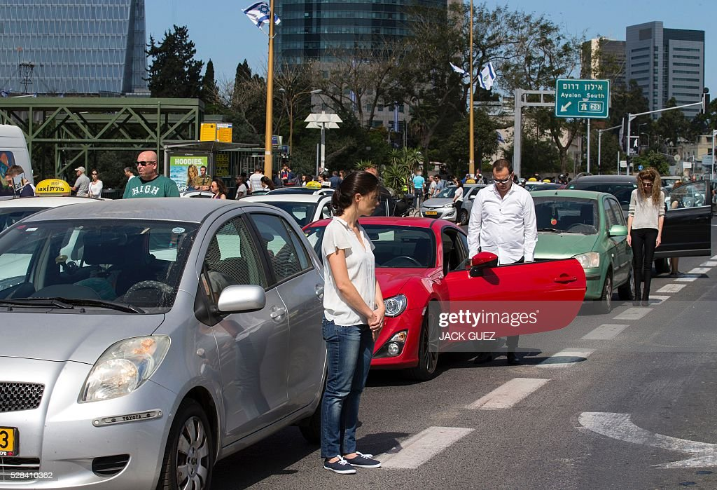 People stop and stand in silence on a highway in the Israeli city of Tel Aviv on May 5, 2016, as sirens wailed across Israel for two minutes marking the annual day of remembrance for the six million Jewish victims of the Nazi genocide. Israel began marking Holocaust Martyrs and Heroes Remembrance Day at sundown on May 4 with a ceremony at the Yad Vashem memorial museum in Jerusalem, which commemorates the Jews killed by the Nazi regime during World War II. / AFP / JACK