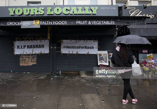 People stop by the floral tributes laid outside the Yours Locally shop where Rashan Charles was arrested by police last week in London England on...