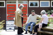 People stop for a chat after casting their vote at a polling station at East Oakley Village Hall in Hampshire an outlying village in the Basingstoke...