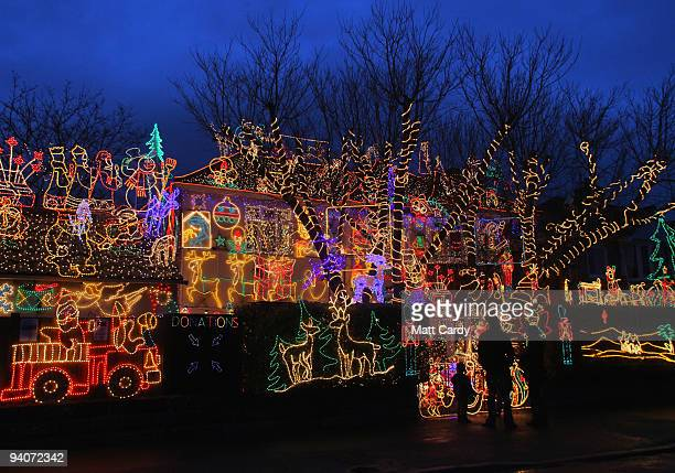 People stop to admire Christmas festive lights displayed on a detached house in a suburbian street in Melksham December 5 2009 in Melksham England...