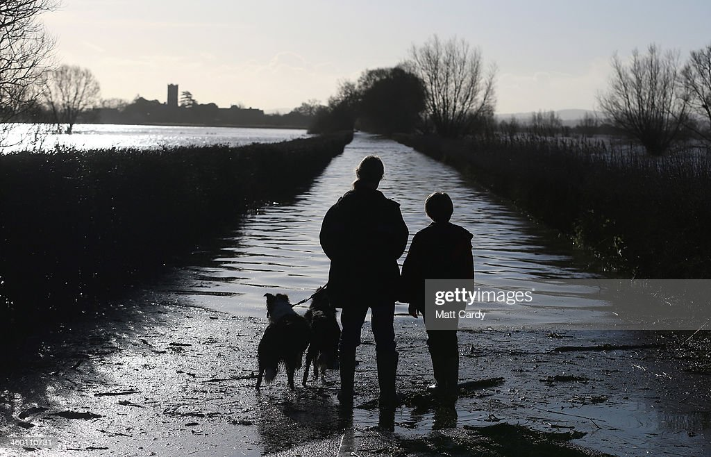 People stop to look at a flooded road leading to village of Muchelney that has been cut off by flood water on January 2, 2014 in Somerset, England. Government ministers are holding a COBRA emergency committee meeting today to discuss the United Kingdom's response to recent flooding.