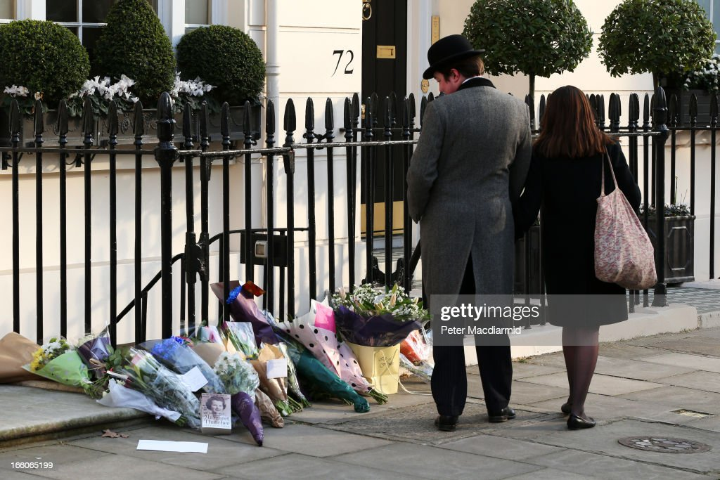 People stop to look at floral tributes outside the residence of Baroness Thatcher in Chester Square on April 8, 2013 in London, England. Lord Bell, spokesperson for Baroness Margaret Thatcher, announced in a statement that the former British Prime Minister died peacefully following a stroke on 8th April, aged 87.