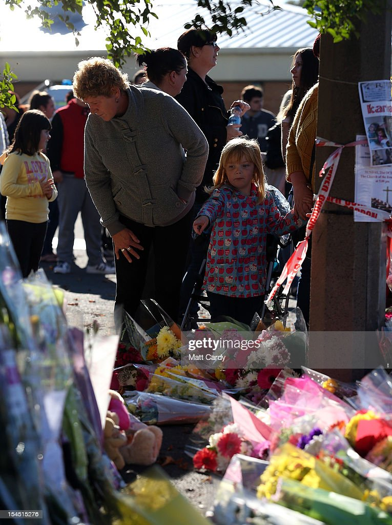 People stop to look at flowers as they attend a local community memorial vigil outside Ely Fire Station for 32-year-old, Karina Menzies, who was killed in a hit-and-run collision on October 21, 2012 in Cardiff, Wales. Detectives are questioning a 31-year-old man arrested on suspicion of murder after a series of hit-and-runs in Cardiff that left a woman dead and 13 people injured. Nine casualties, five of them children, are still in hospital. Two adults are in critical but stable conditions.