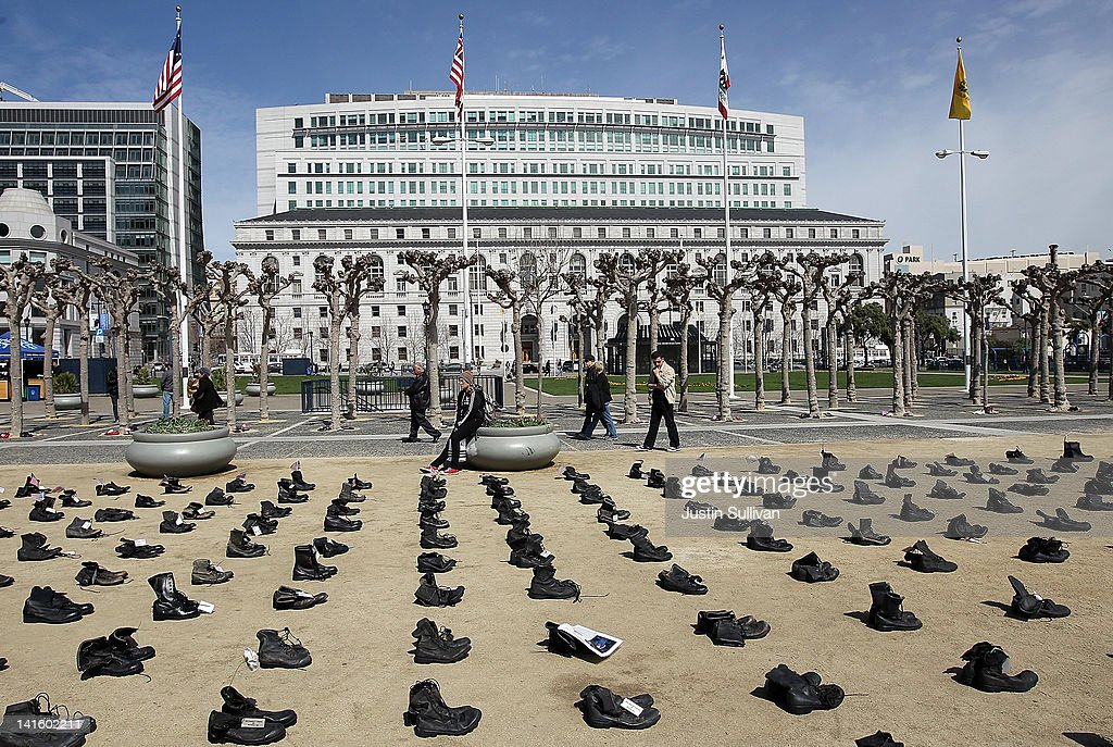 People stop to look at rows of combat boots that are part of the 'Eyes Wide Open' exhibit in front of San Francisco City Hall on March 19, 2012 in San Francisco, California. The Eyes Wide Open exhibition includes a pair of boots for every one of the 481 California servicemen and women who died in the Iraq war.