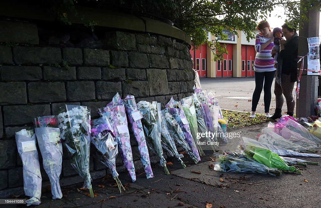 People stop to look at the growing number of floral tributes being left outside Ely Fire Station where a 32-year-old woman, named locally as Karina Menzies, was killed in a hit-and-run collision yesterday on October 20, 2012 in Cardiff, Wales. Detectives are questioning a 31-year-old man arrested on suspicion of murder after a series of hit-and-runs in Cardiff that left a woman dead and 13 people injured. Nine casualties, five of them children, are still in hospital. Two adults are in critical but stable conditions.