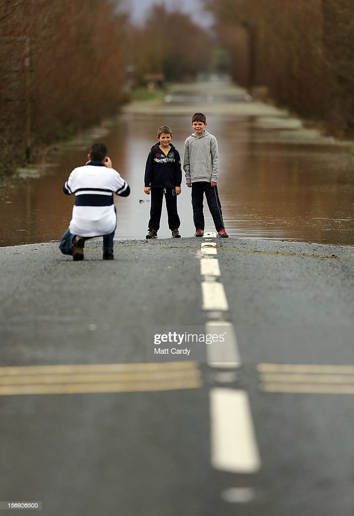 People stop to take a photograph of flood water blocking the A361 on the Somerset Levels at Burrow Bridge, near Taunton, on November 25, 2012 in Somerset, England. Another band of heavy rain and wind continued to bring disruption to many parts of the country today particularly in the south west which was already suffering from flooding earlier in the week.