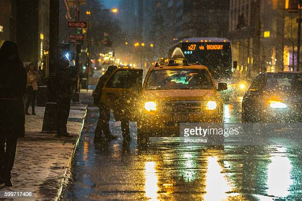 People stopping taxi during snow blizzard, NYC