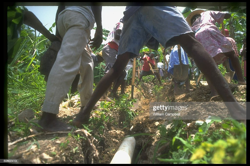 People straddling ditch in field, joining in repairing pipeline w. help of US aid money, prob. agricultural irrigation conduit (no caps).