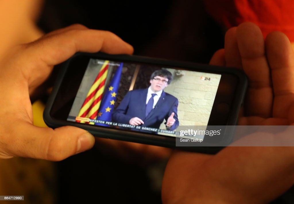 People strain to hear a 9pm statement by Catalan regional president Carles Puigdemont on their smartphones while they gather in front of the Palau de la Generalitat de Catalunya, the building that houses the Catalonian presidency, following a demonstration for Catalan independence to demand the release of imprisoned Catalan leaders Jordi Sanchez and Jordi Cuixart on October 21, 2017 in Barcelona, Spain. The Spanish government announced measures today it will implement in triggering Article 155, which would lead to the imposition of direct rule by Spanish authorities in Catalonia and at least temporarily suspend the region's autonomy. The government also plans to hold Catalan regional elections in January. The moves come after Catalan regional President Carles Puigdemont let a Thursday deadline today pass and threatened to go forward with Catalan independence.