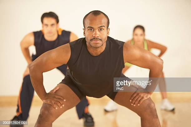 People stretching in exercise class (focus on man in foreground)