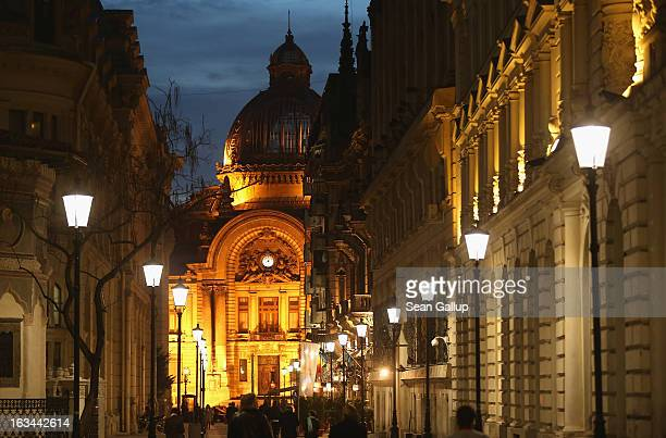People stroll in the Lipscani old town district as the CEC Bank looms behind on March 7 2013 in Bucharest Romania Both Romania and Bulgaria have been...