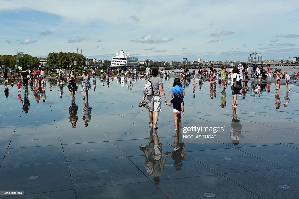 People stroll in the Water Mirror on August 25, 2014 in the southwestern French city of Bordeaux. Hardly eight years after its creation, the Water Mirror is taking an amazing place in the daily lives of Bordeaux residents.